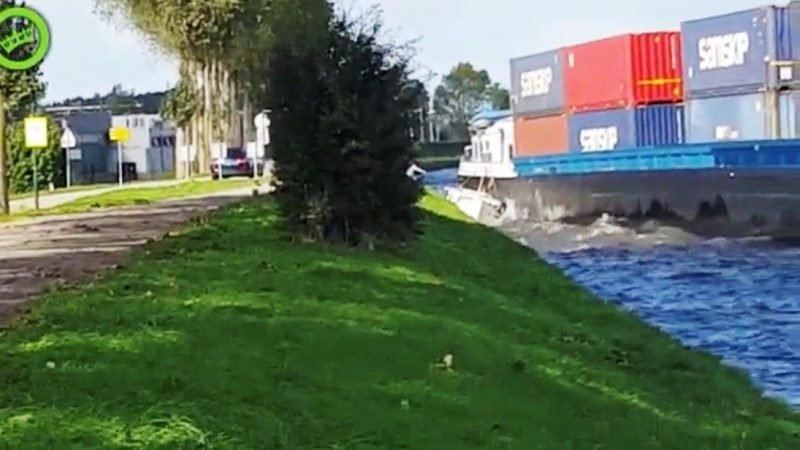 In de bocht van Breukelen drukte het containerbinnenvaartschip een motorjachtje tegen de oever. De opvarenden zagen kans op de wal te springen. (Foto screenshot van Dumpert)