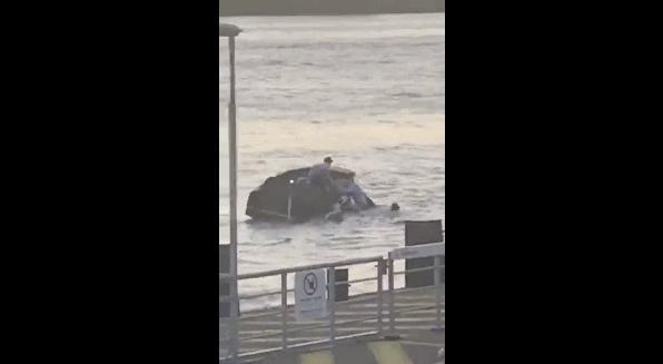 Het omgeslagen bootje met de vier watersporters  wordt na de aanvaring meegenomen door de stevige ebstroom (foto: videostill uit opname van omstander via Het Laatste Nieuws).