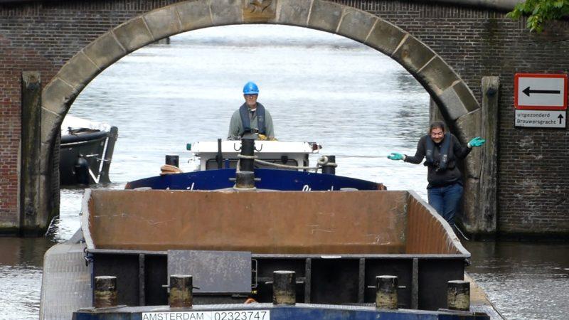 Marc en Carlijn varen door de brug tussen de Prinsengracht en de Brouwersgracht. 'Het vergt wat inventiviteit om zonder schade de stad door te komen.' (Foto Heere Heeresma jr.)