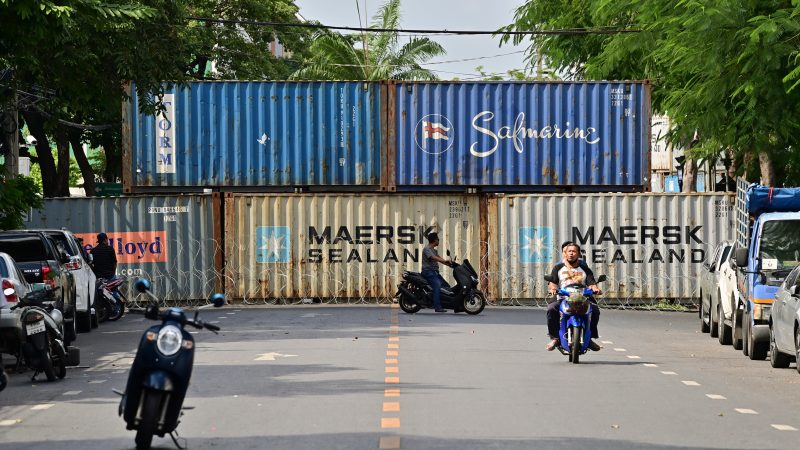 Een straat in Bangkok wordt geblokkeerd door Maersk-containers. (Foto AFP)