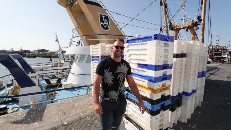 Chauffeur Reyer Vlaming voor een stapel lege viskisten die hij net uit zijn vrachtwagen heeft getakeld. (Foto Bram Pronk)