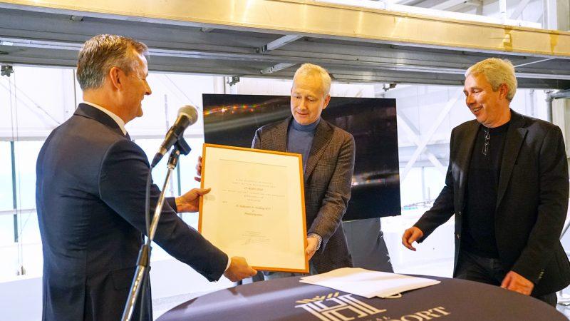 Klaas en Albert Hakvoort ontvangen het predicaat Koninklijk uit handen van commissaris van de koning in Noord-Holland Arthur van Dijk (links). (Foto Hakvoort Shipyard)