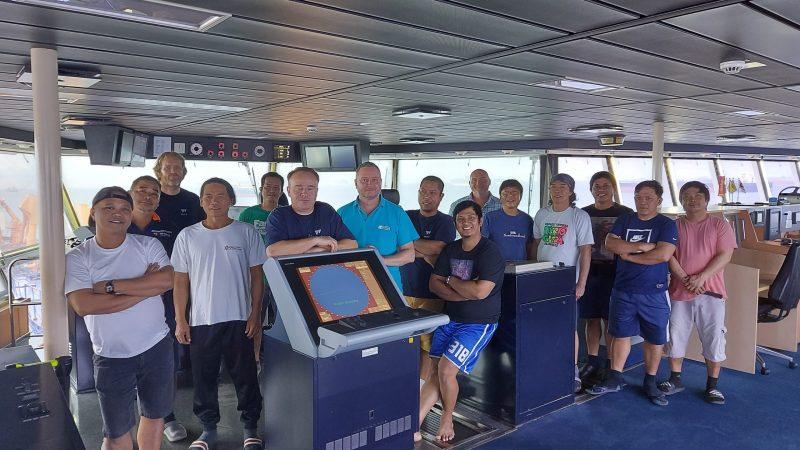 De bemanning van de HAM 318 poseert op de brug. Kapitein Martin Vos: 'Ik heb enorme bewondering voor mijn mensen. Ze gaan er elke dag weer positief tegenaan.' (Foto crew HAM 318)