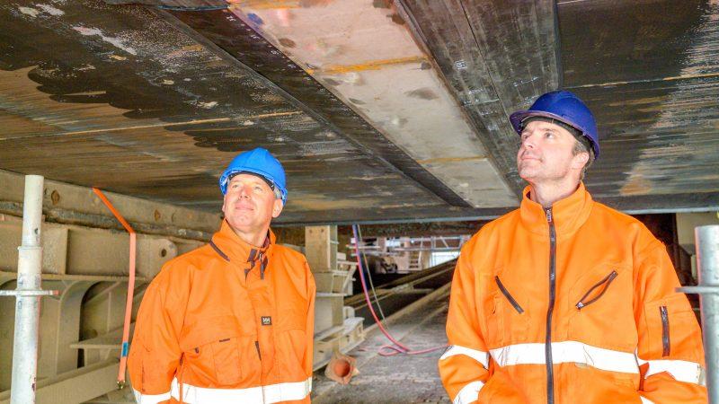 De mede-vennoten annex kapiteins van Tharsis Sea-River Shipping, Jan Albert de Vries en Jan Albert Bosma (rechts) onder de Tharsis bij een van de strips met oscillatoren van MPS luchtsmeringssysteem. (Foto Rob Spaans)