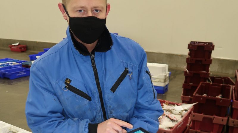 Op de foto voert afslagmedewerker Tim Kuiper de hoeveelheden per kist van de Arnemuidense Eurokotter in.