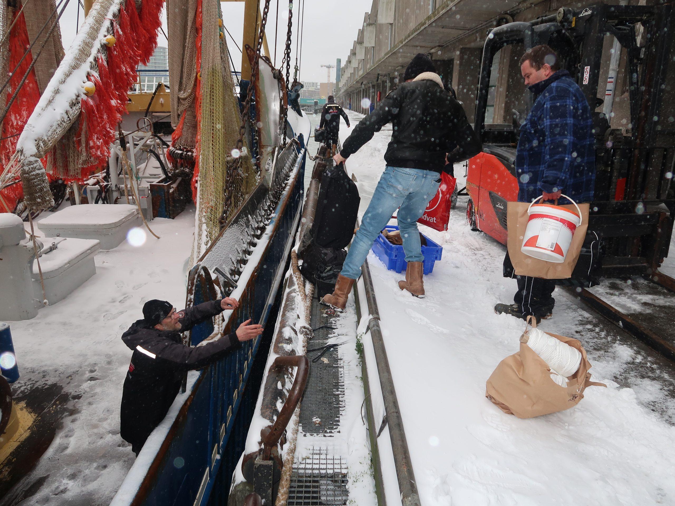 Op de foto geven bemanningsleden Henk Regtop en Dennis Boom (rechts) hun weekendtassen aan schipper Pieter-Aris van der Vis, die reeds in het gangboord staat. (Foto W.M. den Heijer)
