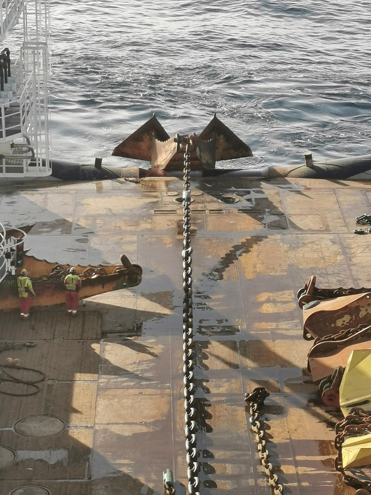 Het 26,5 tons anker op het achterdek van de Island Victory. De twee bemanningsleden links geven een indruk van de grootte van het anker. (Foto Island Offshore)