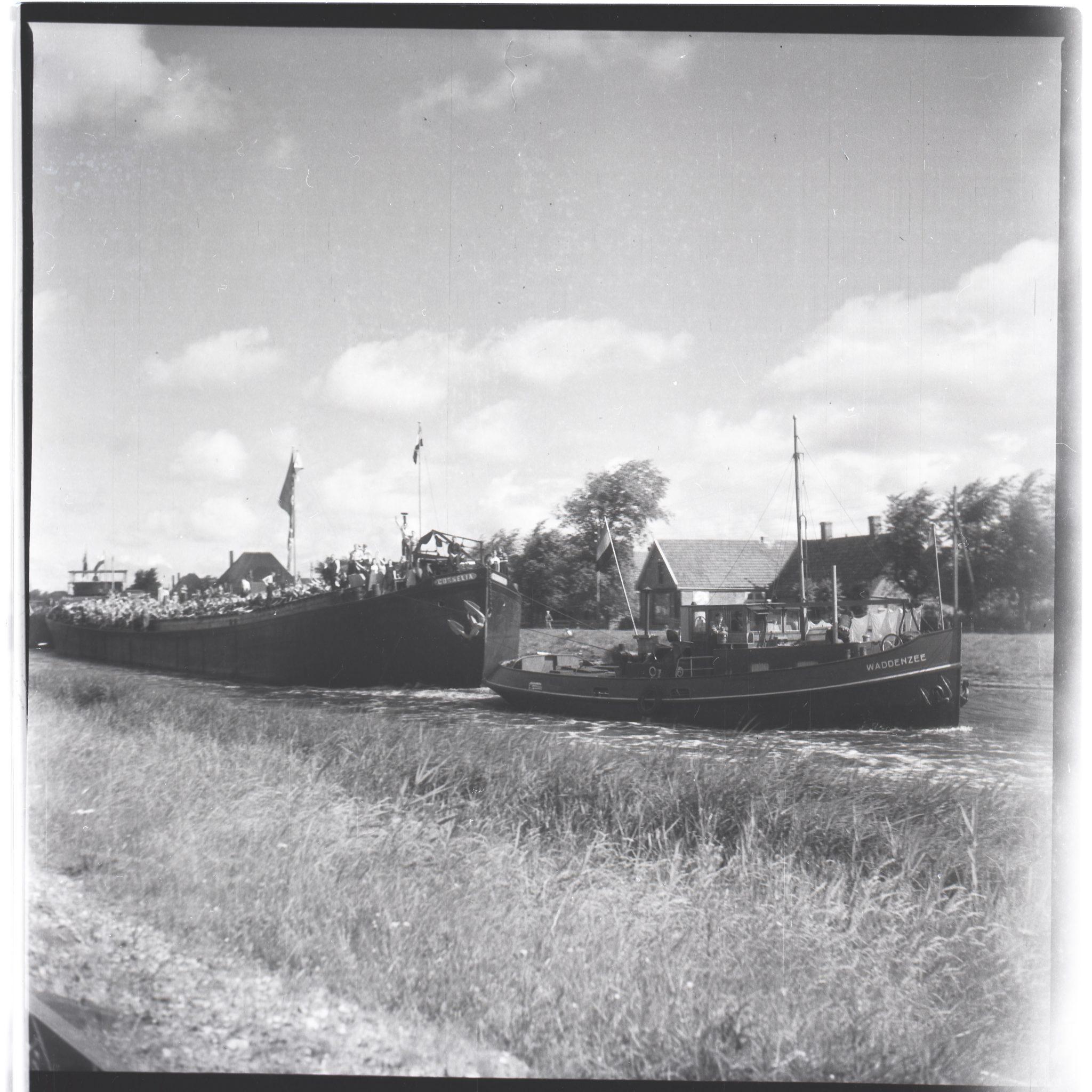 Het sleepschip de Cornelia tjokvol met kinderen als eerste lengte achter de sleepboot op het Noordhollandsch Kanaal onderweg naar Alkmaar. Deze foto is genomen in de zomer van 1945. (Collectie Regionaal Archief Alkmaar)