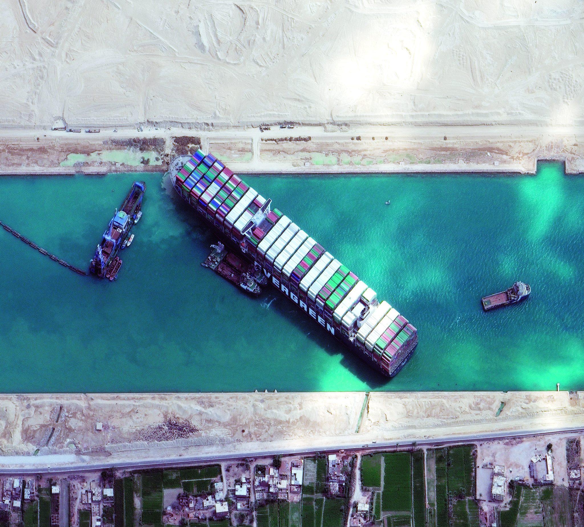 Vanuit de lucht is goed te zien hoe de Ever Given zich volledig heeft vastgeboord in de oever van het Suezkanaal. Foto Maxar