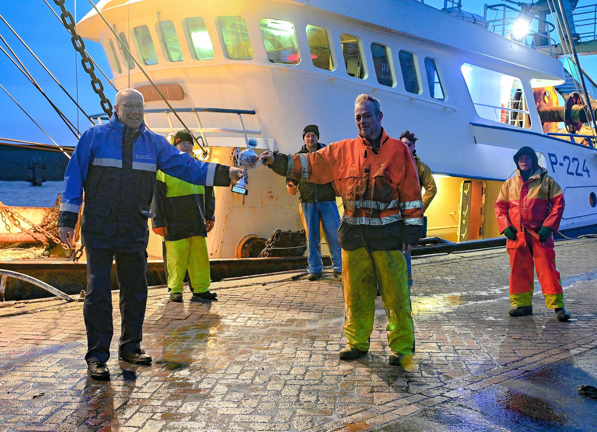 Met inachtneming van de coronaregels ontvangt schipper Nico Gorter (rechts) de 'communicatiebeker' uit handen van havenbeambte Andries Koornstra. (Foto Joachim de Ruijter)