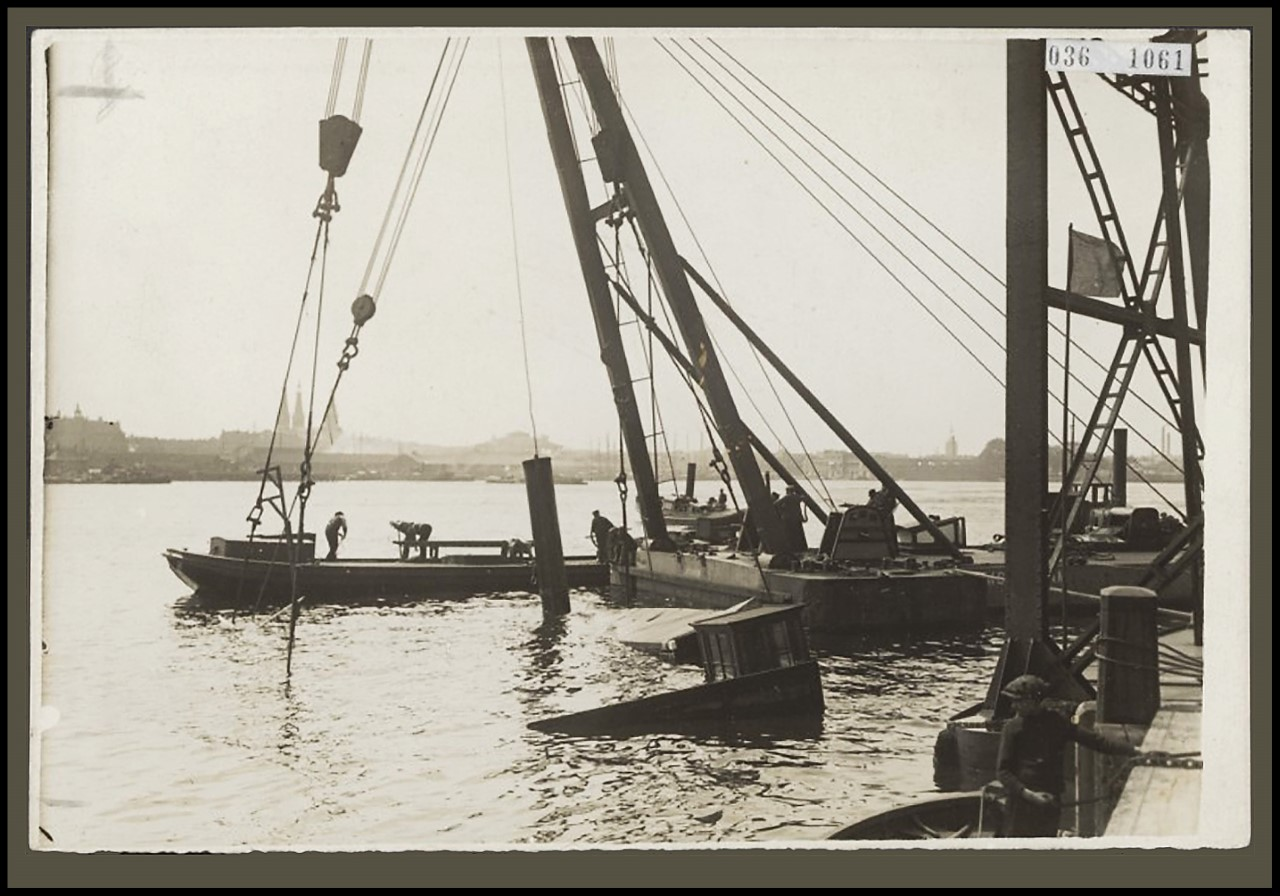 Bergingswerkzaamheden van de Amsterdamse kettingboot in 1920. Gezien de lengte van de schoorsteen die boven water uitsteekt, is het schip al 1 à 2 meter gelicht.