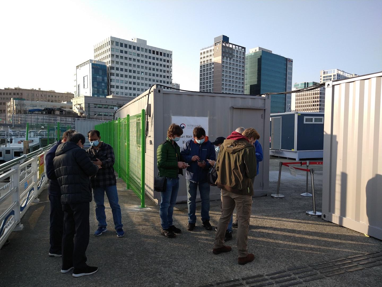 Coronatestlocatie in Busan. Iedereen moet een Koreaanse simkaart installeren en dat valt niet mee.