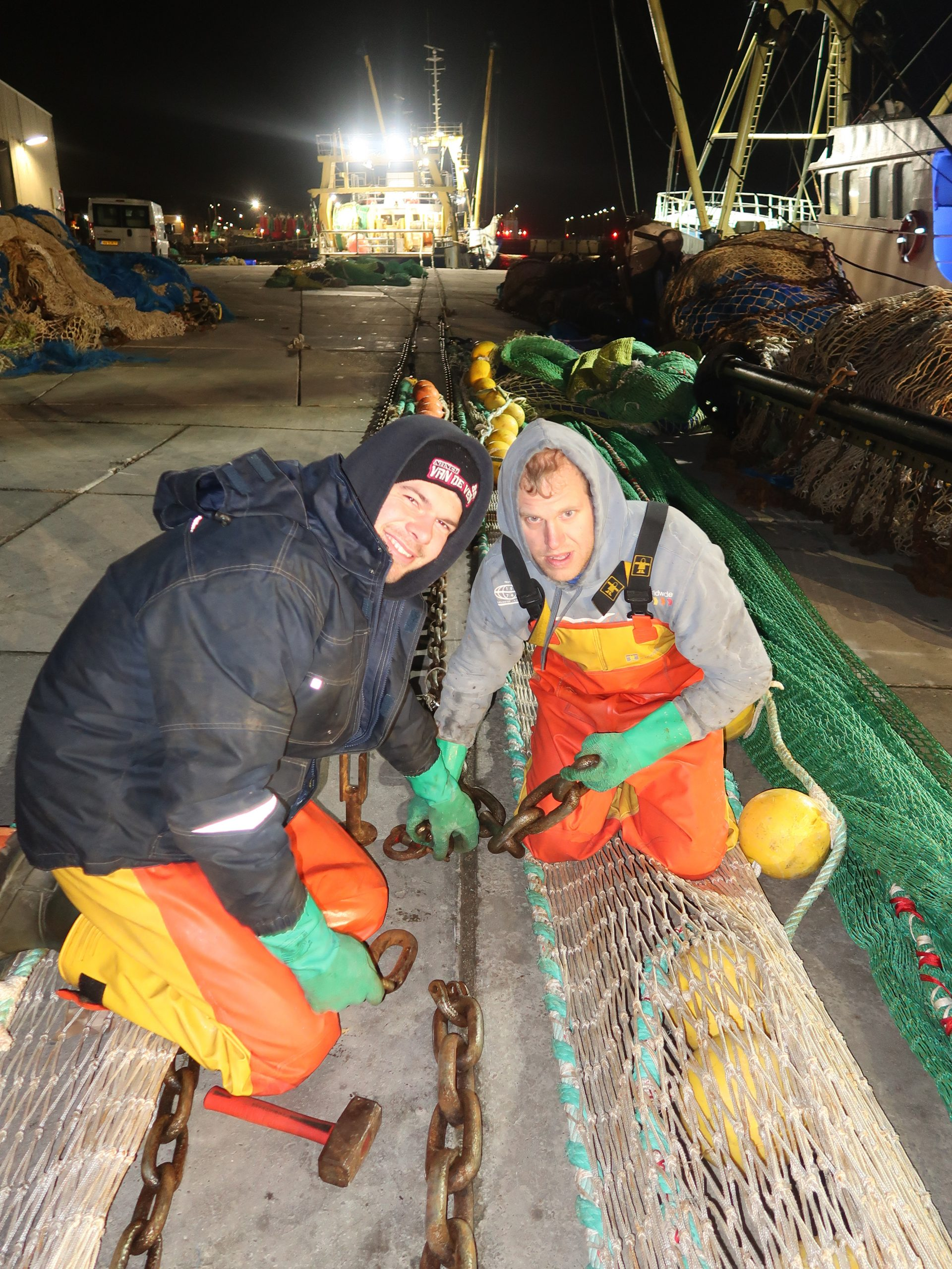 Matrozen Pojk van de Gruiter (links) en Paco de Visser repareren in de vroege ochtend het flyshootnet, zodat het weer picobello in de schuur kan worden opgeborgen tot de boomkorvisserij in het Bristolkanaal weer ten einde is. (Foto W.M. den Heijer)