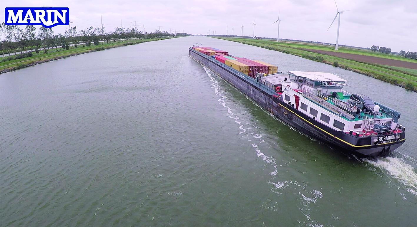 Op deze foto van MARIN is goed te zien dat zelfs een binnenvaartschip geladen met containers al met een hoek op de waterweg moet varen om de winddruk tegen te gaan.