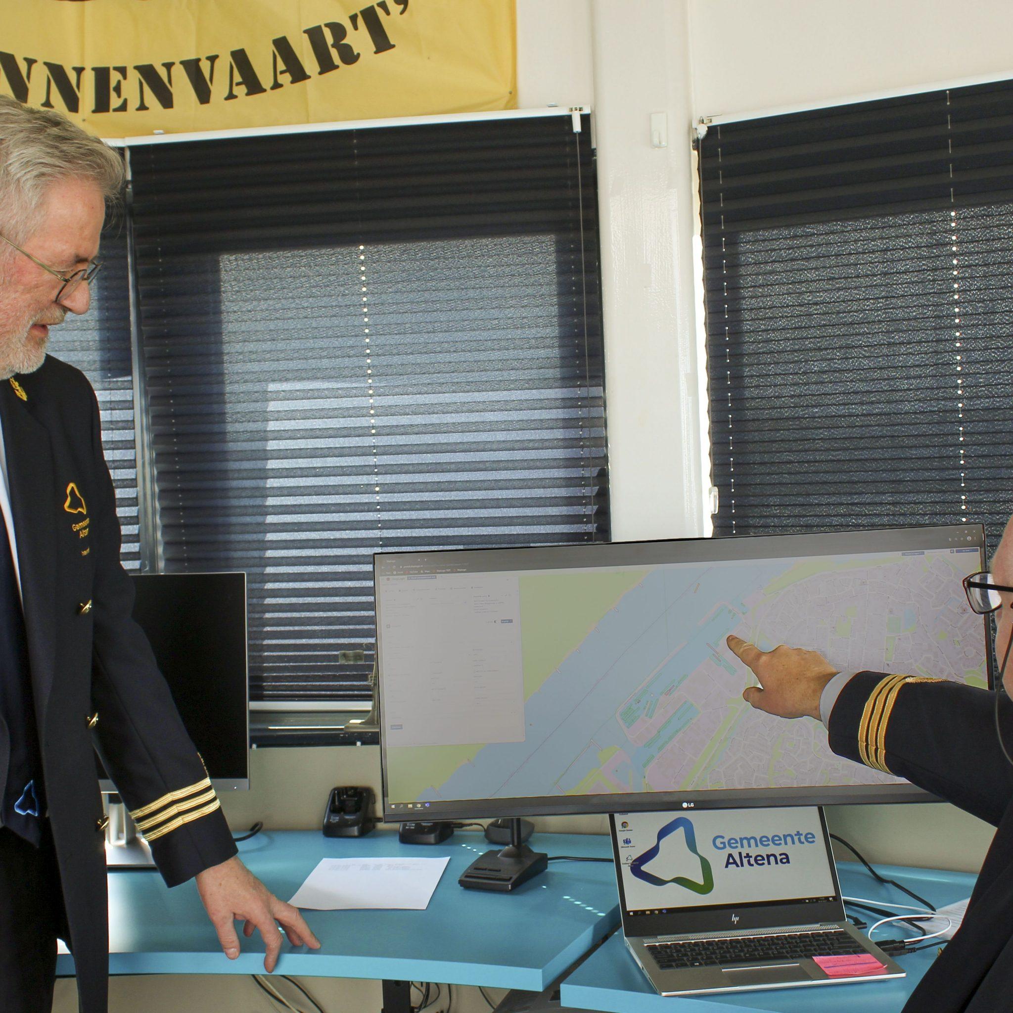 Havenmeesters Lou Goedel (links) en Jan bekijken de interactieve kaart. (Foto gemeente Altena)