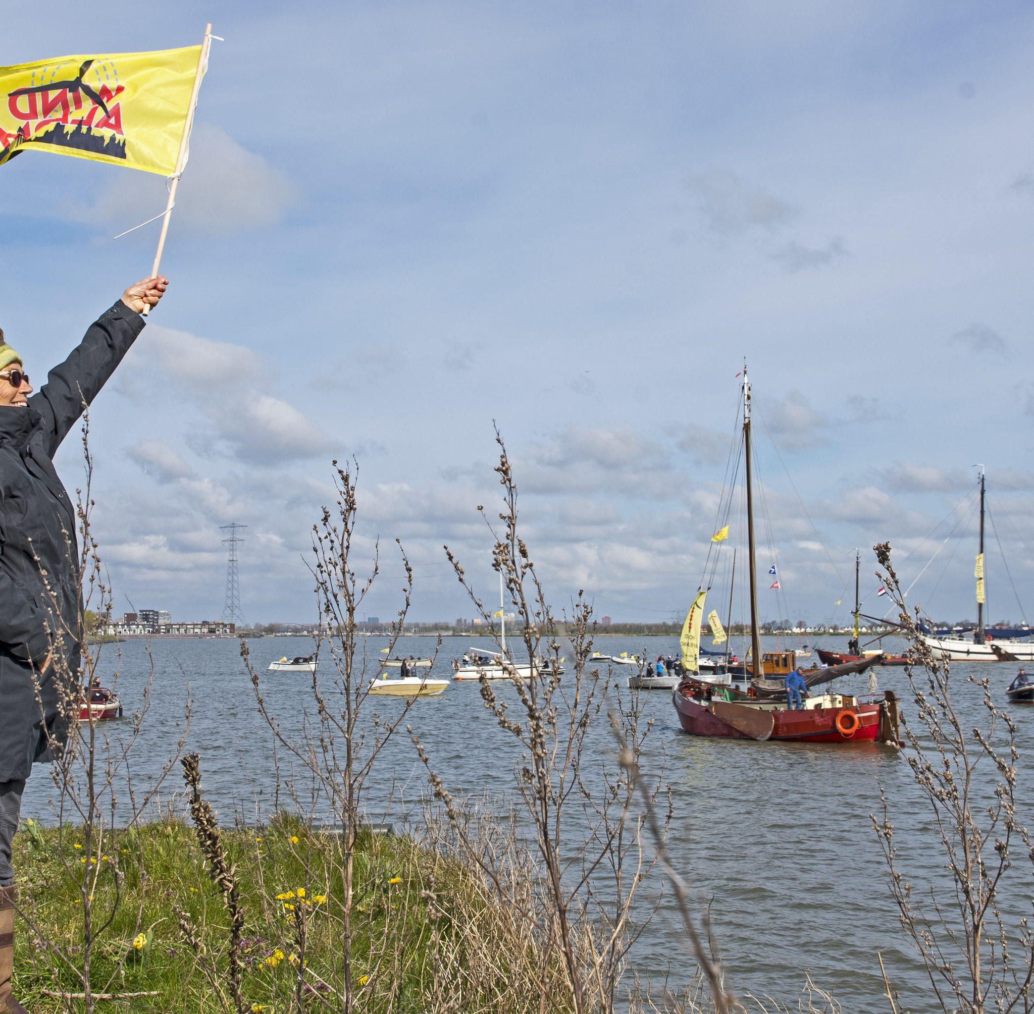 Zo'n vijftien grote en kleine schepen voeren zaterdag naar het IJmeer voor Haveneiland West om te protesteren tegen de voorgenomen plaatsing van 17  mega windmolens. Foto Hajo Olij