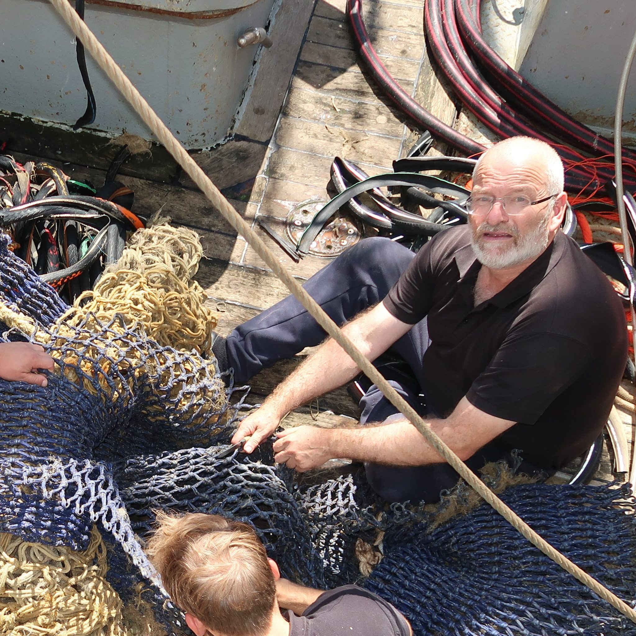 Nico van der Plas bezig met herstel van de netten aan boord van de KW-5. (Foto W.M. den Heijer)