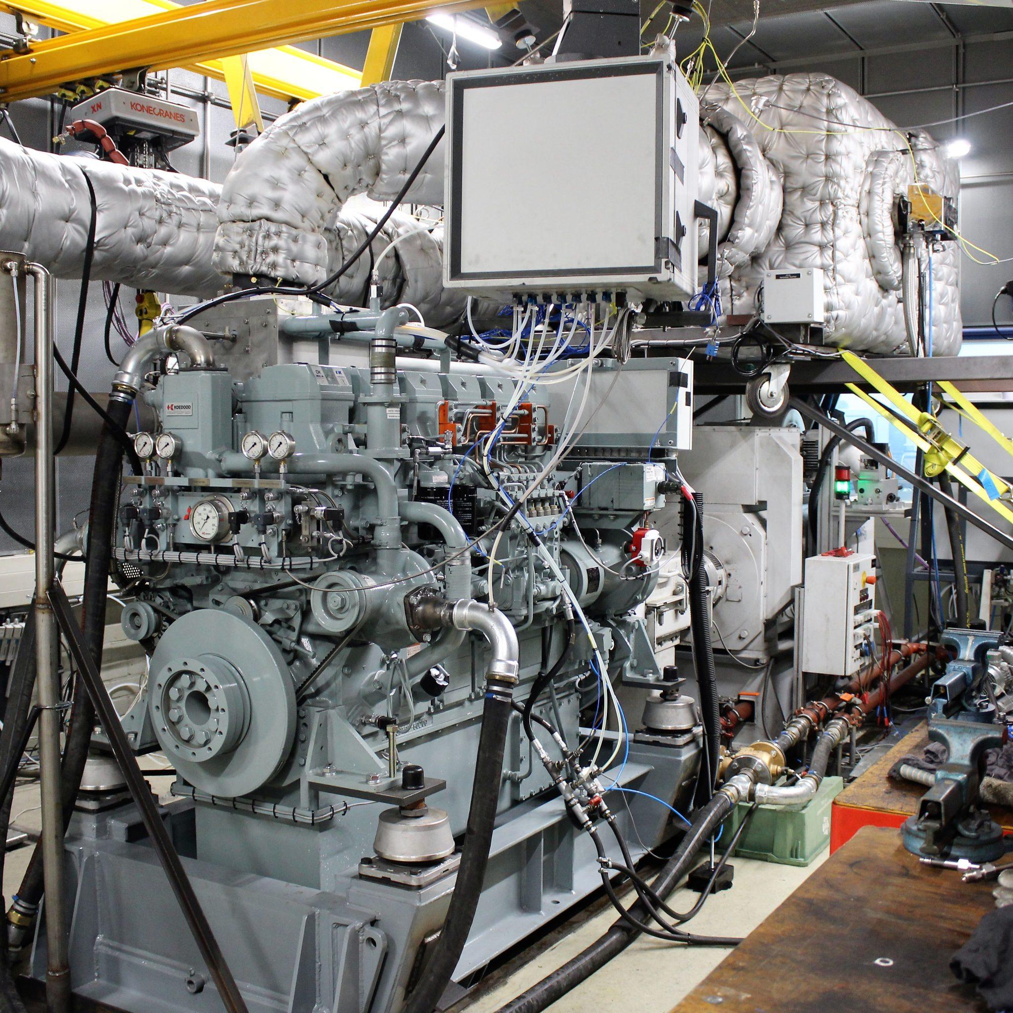 De zescilinder S6R-MPTK/ MPTAW op de testbank van het Power Test Centre van TNO Automotive in Helmond. Met de Stage V-certificering van deze motor wordt de tot 16 cilinders doorlopende MPTK/MPTAW motorenfamilie (470 tot 1250 kW) in één keer gecertificeerd. Op de foto links Jeroen van Schaik van TNO Helmond en rechts Richard Suurbach van Koedood Dieselservice. (Foto Hans Heynen)