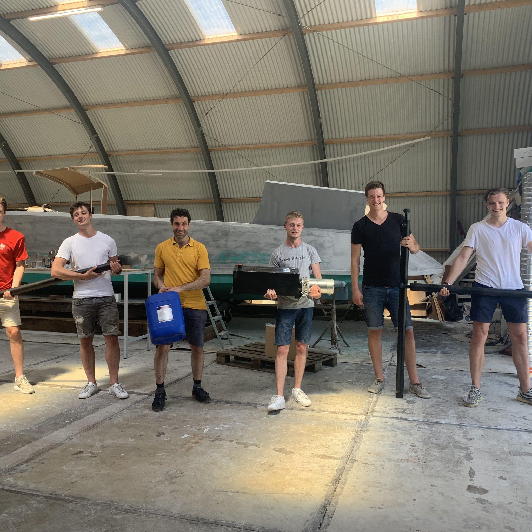 Vlnr: Sjoerd den Boer, Luuk Breggemans, Elio Barone, Nick van Hugten, Jelle Jongebreur en Ruben van Aalst met de hydraulische onderdelen voor de bootlift. Op de achtergrond de Futuro in aanbouw. (foto: T. vd Berg)