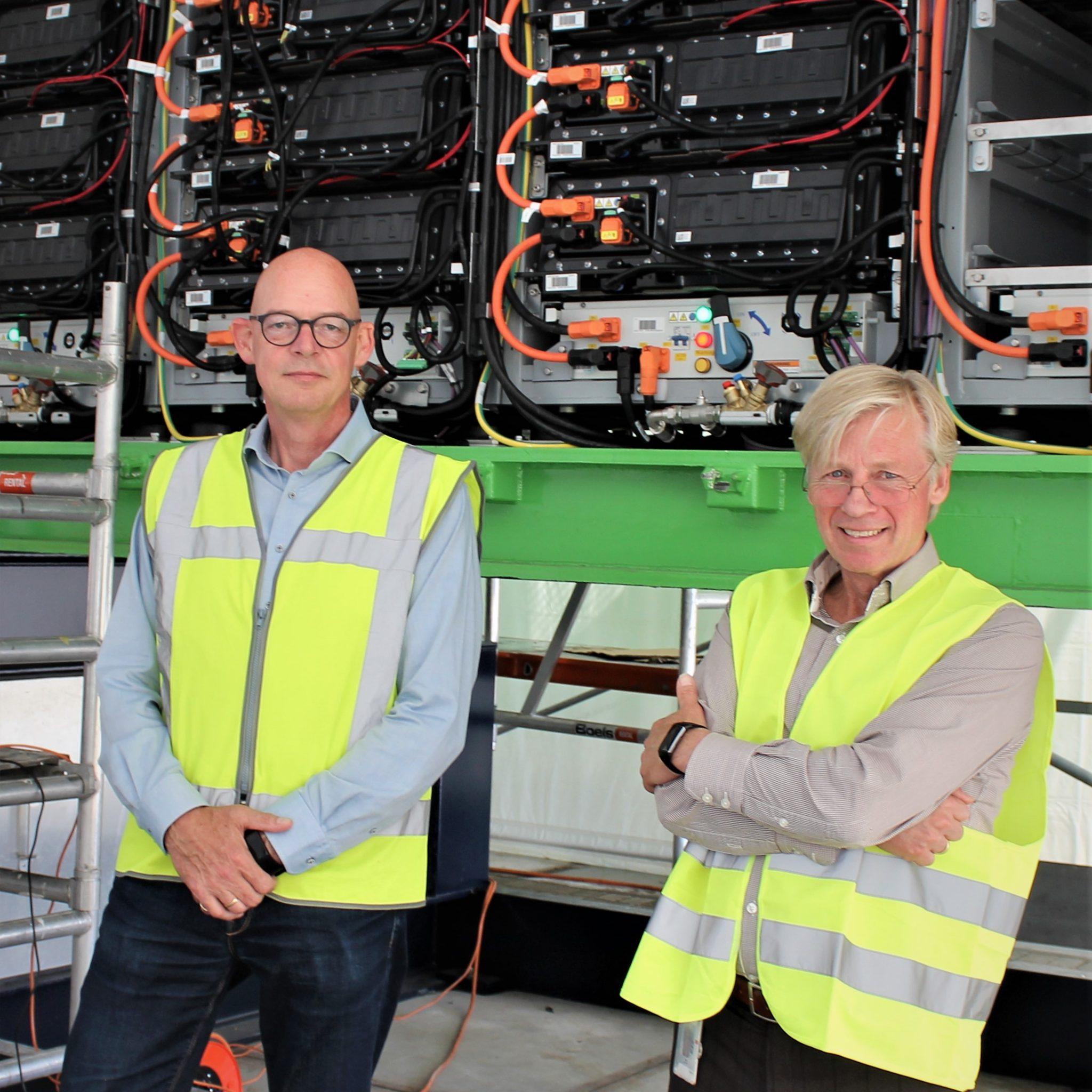 Leon Sluiman (links) en Teus van Beek bij de eerste operationele ZESpack batterijcontainer. Hij staat hier bij de laadinstallatie op het Alpherium in Alphen aan den Rijn. Daar kunnen twee batterijcontainers in 2,5 tot 3 uur volledig worden opgeladen. De laadinstallatie kan ook worden gebruikt voor het opladen van batterijen in elektrische vrachtwagens. (Foto Hans Heynen).