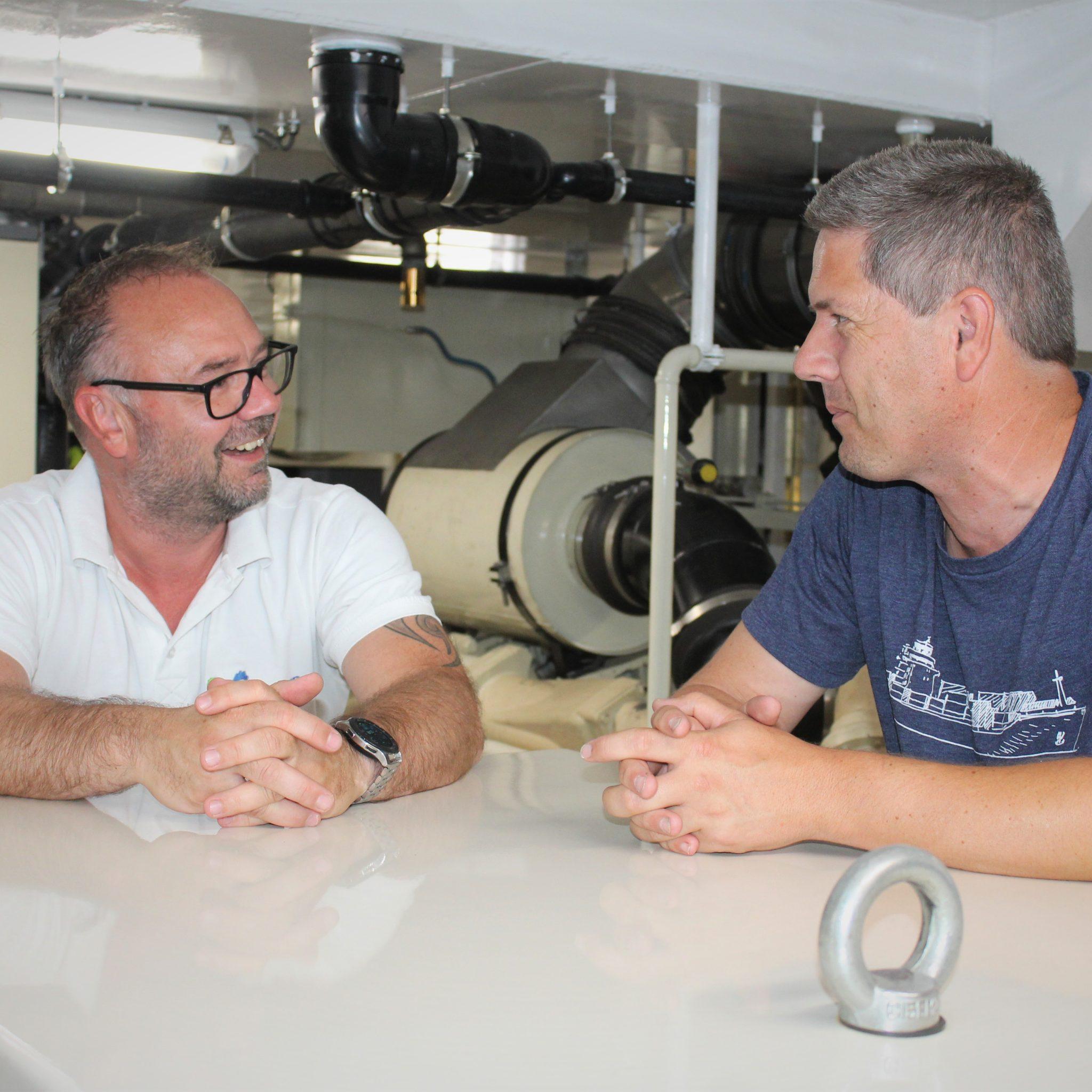 Salesmanager Jelle Westerhof van Emigreen en schipper/eigenaar Jacob Verdonk van het ms Anda in de machinekamer van de Anda.