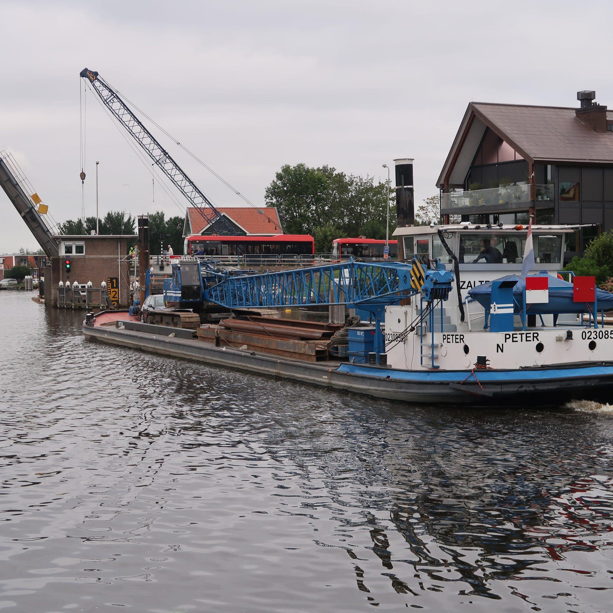 Op weg naar Harderwijk passeert het kraanschip Peter de brug bij Ouderkerk aan de Amstel. (Foto W.M. den Heijer)